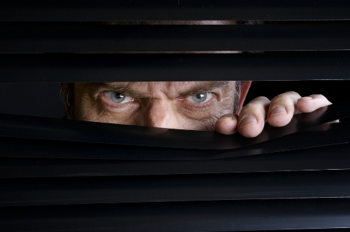 man-spying-through-blind-shutterstock-510px