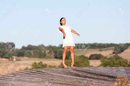 27902476-a-young-woman-is-balancing-on-the-edge-of-a-wooden-structure-named-yan-she-is-on-tip-toes-and-she-ri-stock-photo